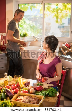 Nice couple cooking together a vegetable meal in the kitchen by a sunny day. The woman is cutting a tomato and the grey haired man is doing the dishes. They looks happy, wearing casual clothes. - stock photo