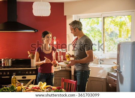Nice couple in casual clothes cooking vegetables from the market in a red kitchen. The woman is stirring the sauce in a white pan while the grey hair man is doing the vinaigrette with olive oil. - stock photo