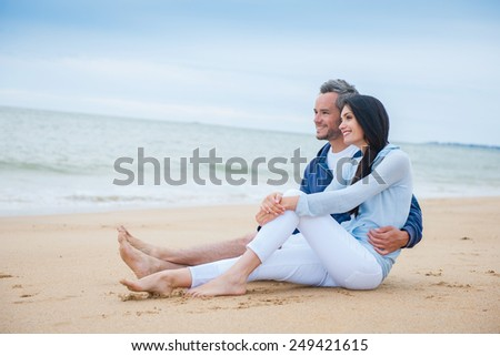 nice couple sitting in the sand in casual clothes, looking at the ocean - stock photo