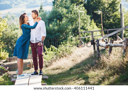 Nice couple standing together, outdoor, countryside. Girl embracing her boyfriend. Woman wearing blue dress and light blue shoes and man wearing white shirt, claret trousers and black shoes. Full body - stock photo