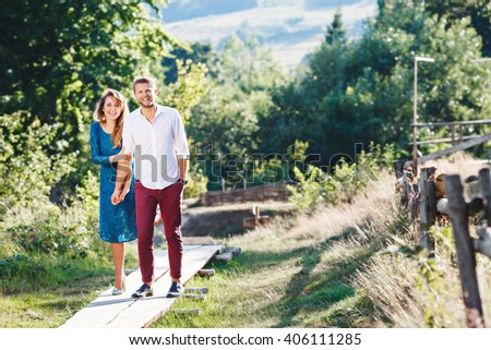 Nice couple standing together, outdoor, in the countryside. Woman wearing blue dress and light blue shoes and man wearing white shirt, claret trousers and black shoes. Girl holding man's hand. - stock photo