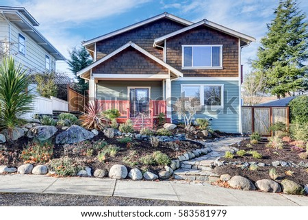 nice craftsman home exterior on blue sky background well kept frontyard with natural stone landscape