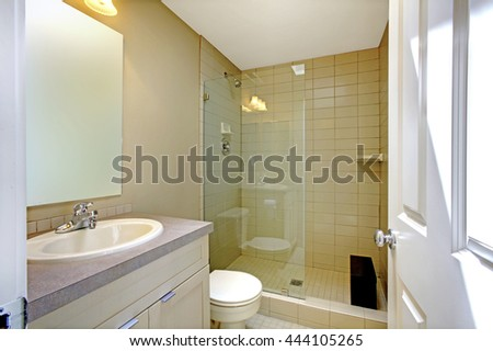 Nice creamy bathroom interior with glass shower, toilet and white cabinet with mirror.