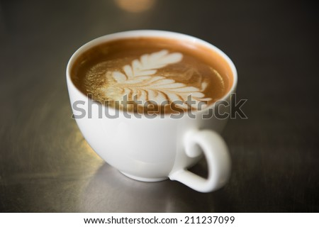 Nice cup of aromatic delicious coffee with the pattern standing on the table - stock photo