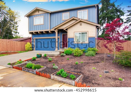 Nice curb appeal of blue house with front garden. House exterior. - stock photo