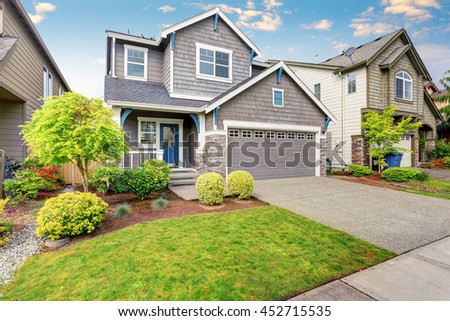 Nice curb appeal of two level house, mocha exterior paint and concrete driveway. View of cozy small porch - stock photo