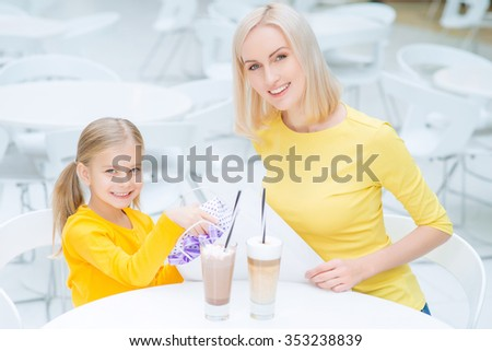 Nice day. Content smiling  mother and daughter sitting at the table and drinking coffee while resting in the cafe - stock photo