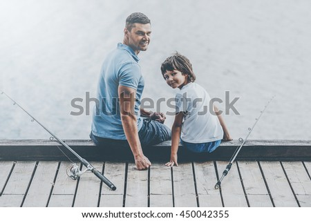 Nice day for fishing. Rear view of father and son sitting at the quayside and looking over shoulder while fishing rods laying near them - stock photo