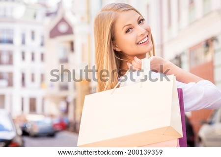 Nice day for shopping. Rear view of beautiful young cheerful woman holding shopping bags and looking over shoulder while standing outdoors - stock photo