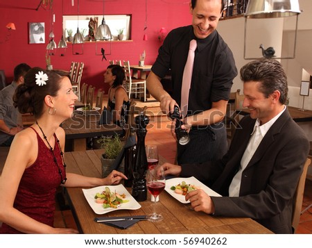 nice dinner in a restaurant - waiter offers pepper - stock photo
