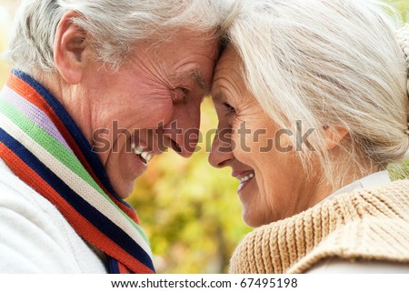 nice elderly couple in a autumn park - stock photo