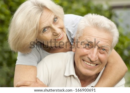 Nice elderly couple in the park on a background of green trees and bushes