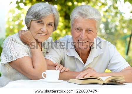 Nice elderly couple sitting at table during summer - stock photo