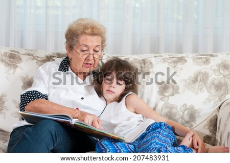 Nice elderly woman grandmother reading story to sweet young granddaughter - stock photo