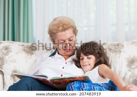 Nice elderly woman grandmother reading story to sweet young granddaughter. Family and education concept.