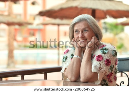 Nice elderly woman sitting at cafe table - stock photo