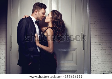 Nice elegant couple next to the door - stock photo