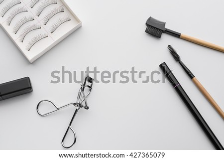 Nice equipment for make-up used for application on eyes. Special curler, mascara and soft brushes for treatment of lashes and brows. False eyelashes set in paper box. - stock photo