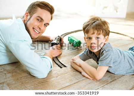 Nice family photo of little boy and his father. Boy and dad playing with trains on wooden floor - stock photo