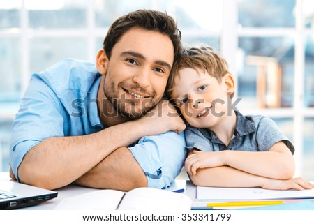 Nice family photo of little boy and his father. Boy and dad sitting at room with big window and looking at camera - stock photo
