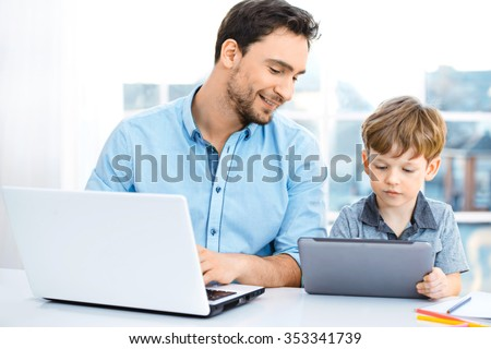 Nice family photo of little boy and his father. Boy and dad sitting at room with big window. Young man working with laptop while boy using tablet computer - stock photo