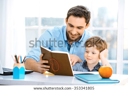 Nice family photo of little boy and his father. Boy and dad sitting at room with big window. Young man helping his son to make homework - stock photo