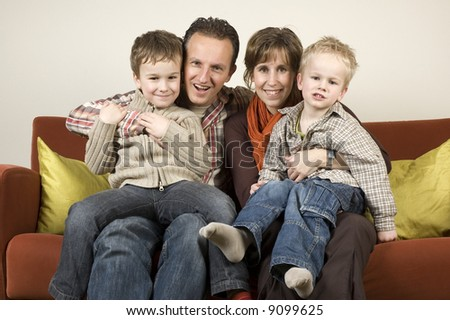 Nice family picture, sitting together on a couch.