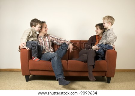 Nice family picture, sitting together on a couch. - stock photo