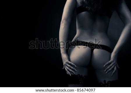 Nice female backside on dark background - stock photo