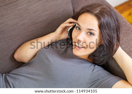 Nice female lying on a sofa and phoning