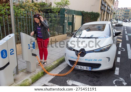 NICE, FRANCE - APRIL 11, 2015: A woman is programming the Auto Bleue charging station to electrically charge a Renault Zoe electric car in Nice, France. - stock photo