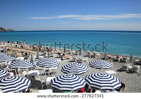 NICE, FRANCE - APRIL 30, 2015: Beach and ocean of Nice on April 30, 2015 in Nice, France. It is a popular tourist resort on French Riviera. - stock photo
