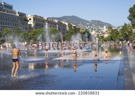 NICE, FRANCE - AUGUST 27, 2014: Lovely fountain in the heart of Nice. Many kids are getting excited at water springing up at the fountain surrounded by beautiful historic buildings and urban park - stock photo