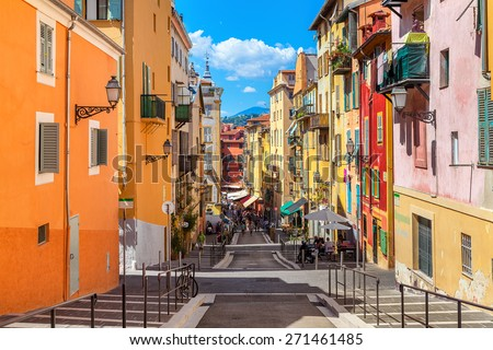 NICE, FRANCE - AUGUST 23, 2014: Narrow street in old tourist part of Nice - fifth most populous city and one of the most visited cities in France, receiving 4 million tourists every year. - stock photo