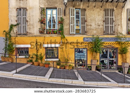 NICE, FRANCE - AUGUST 23, 2014: Pedestrian walkway along house with small gift shop in old Nice - fifth most populous and one of most visited cities in France with 4 million tourists every year. - stock photo