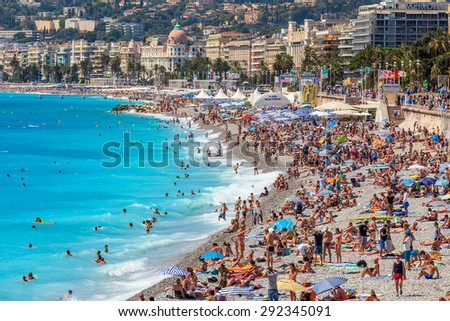 NICE, FRANCE - AUGUST 23, 2014: People on the beach of Nice - fifth most populous, second-largest on French Mediterranean coast and one of most visited cities with 4 million tourists every year. - stock photo