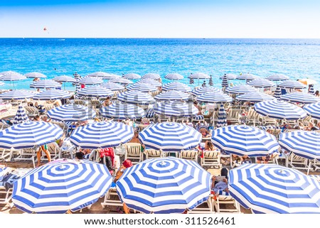 NICE, FRANCE - AUGUST 23: Tourists enjoy the good weather at the beach on August 23, 2015 in Nice, France. The beach and the waterfront avenue, Promenade des Anglais, are full almost all the year.