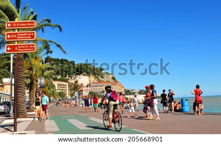 NICE, FRANCE - JULY 27, 2013: Crowds of tourists relax on the beach of French Riviera at the Mediterranean Sea. - stock photo