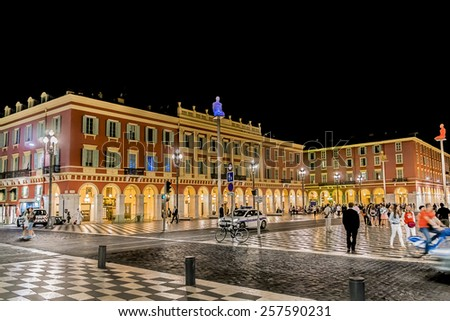 NICE, FRANCE - JULY 7, 2014: People hang around Place Massena at night. Place Massena - Main Square of the city and it is used for concerts and other events which take place in the city. - stock photo