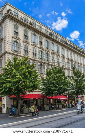 "NICE, FRANCE - JULY 7, 2014: View of Avenue Jean-Medecin. It constitutes the city's main shopping street and is called ""The Avenue"" by residents."