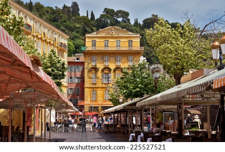 NICE, FRANCE - JUNE 6, 2014: Old building and a cafe in the Cours Saleya. The Cours Saleya is a place of outdoor restaurants, boutiques and a market.  - stock photo
