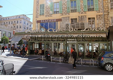 NICE, FRANCE - MAY 13, 2013: Outdoor french cafe in old building on the main city street - Jean Medecin Avenue in Nice,France. Sun beams