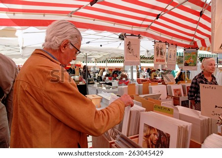 NICE, FRANCE - MAY 13, 2013: The Cours Saleya at the French Riviera famous of antique market every Monday in Nice, France. Customers looking at collectibles of vintage posters. Selective focus - stock photo