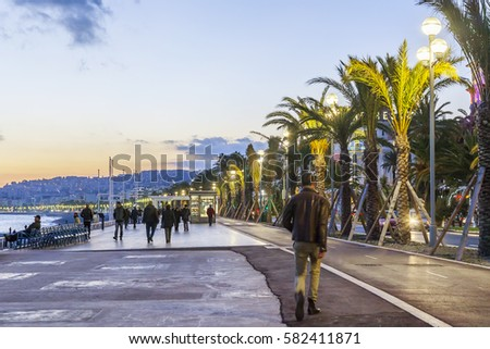 NICE, FRANCE, on JANUARY 6, 2017. People go on Promenade des Anglais in the evening.