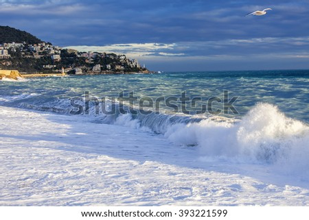 NICE, FRANCE, on JANUARY 13, 2016. Sea landscape. The line of a surf and storm waves lit with beams of the sunset sun.