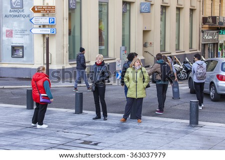 NICE, FRANCE, on JANUARY 7, 2016. Typical urban view in the sunny winter afternoon. People go down the street