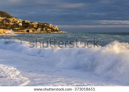 NICE, FRANCE - on JANUARY 8, 2016. View of the line of a surf, wave, beach and sky and embankment in a distance in beams of sunset