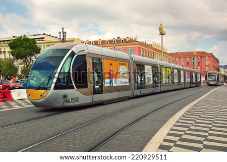 NICE, FRANCE - SEPTEMBER 12, 2014: Contemporary tram passing on Place Massena - one of the main city squares, place for carnivals, concerts, parades, traditional celebrations and other public events. - stock photo