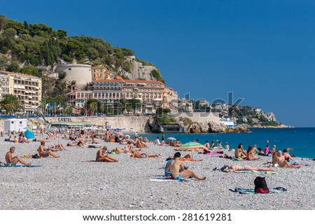 Nice, France - September 4, 2014: People on the beach on a sunny day. Castle Hill in the background.