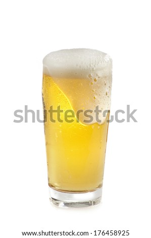 nice fresh glass of beer with foam pouring over - stock photo